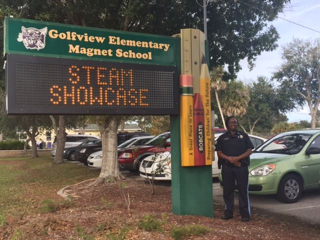 Office Holmes in Front of Golfview Elementary Magnet School Sign