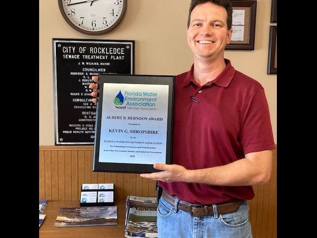 Kevin Shropshire, Pretreatment Coordinator, holding an award plaque